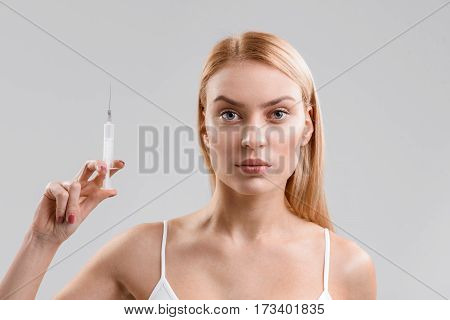 I am ready to fight with aging. Serious young woman is standing and holding syringe with botox. Isolated on background