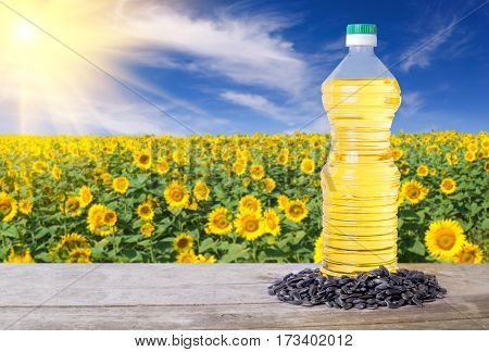 Sunflower oil in plastic bottle and seeds on wooden table with blossom field on the background. Sunflower field with blue sky and sun. Photo with copy space. Agriculture and harvest concept