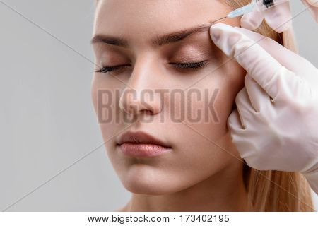 Calm young woman is getting botox injection under her eyebrow. Her eyes are closed with tranquility. Isolated and copy space in left side