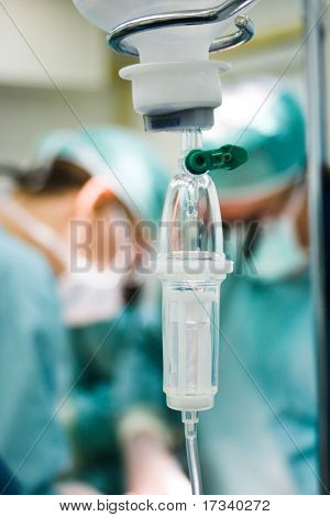 intravenous drip in operation room with surgeons on background poster