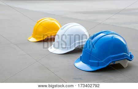 Tree safety plastic helmets : white yellow and blue on concrete floor at under construction area with copy space. Focus on the blue hat.