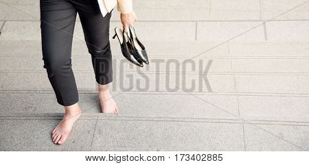 Young woman rubbing her sore tired feet. Businesswoman in office style clothes carrying in hand her high heel shoes walking barefoot step up legs close-up copy space or background for banner