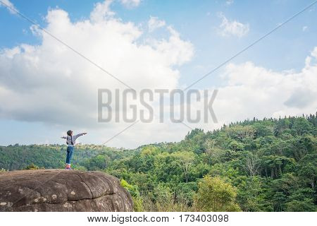 Joyful Young Asian girl holding hands and breathing fresh air outdoors. Healthy active lifestyle concept. Copy space. Pha Koo Rak Phu Hin Rong Kla national park Phitsanulok Thailand.