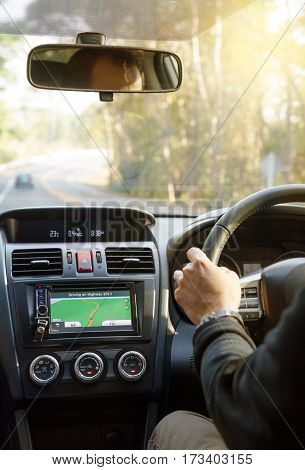 Asian man driving a car with navigation device for traveling. Close up of hand of businessman and gps touchscreen focus on hand holding steering wheel.