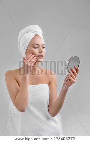 My skin is perfect. Sensual girl is touching her face and looking at mirror with satisfaction. She is standing wrapped by towel. Isolated