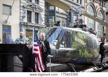 NEW YORK - NOV 11, 2016: Steve Maloney and his mixed-media sculpture Take Me Home Huey, a restored US Army Huey air ambulance helicopter from the Vietnam War in the Americas Parade on Veterans Day.