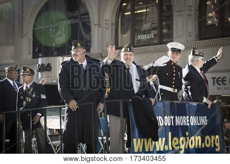 NEW YORK - 11 NOV 2016: Vets from the American Legion wave from their parade float in the annual Americas Parade up 5th Avenue on Veterans Day in Manhattan.