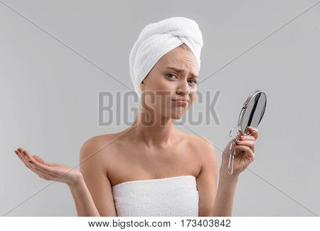 Sad girl is dissatisfied with her skin. She is holding mirror and looking at camera with despair. Isolated