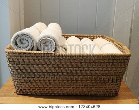 Pile of cloth hand towel table napkin handkerchief on the basket in spa bath room toliet with blur white wooden wall background sideview