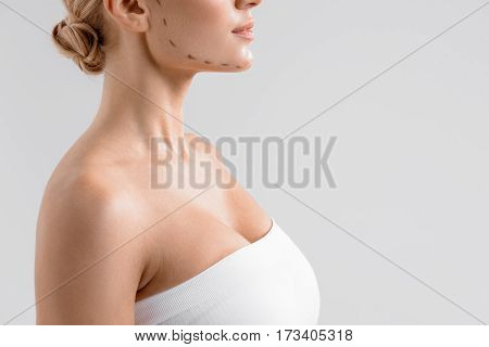 I want to be perfect. Young woman is standing with drawn correction lines on her face. Isolated and copy space in right side