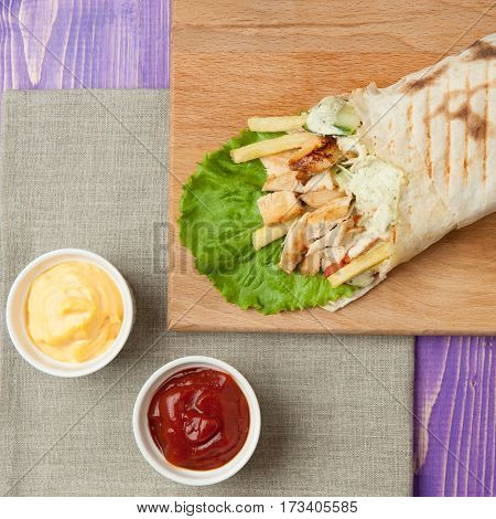 middle eastern shawarma on wooden board and two white cups with ketchup and cheese on purple wooden table