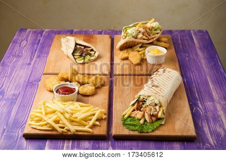 french fries and nuggets Arabic shawarma Greek gyro and pita with chocolate and kiwi on four wooden boards on a wooden purple table for four person from side view