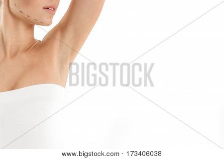 Beauty concept. Close up of young woman standing and raising her arm while showing armpit. She has correction lines drawn on her face. Isolated and copy space in right side