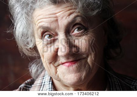 A portrait of a thoughtful granny on a black