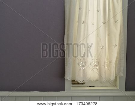 White Lace satin curtain hanging on window with sunlight semitransparent vintage light purple wall decoration interior room