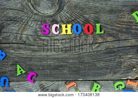 Wooden multicolored letters on a gray surface the word school