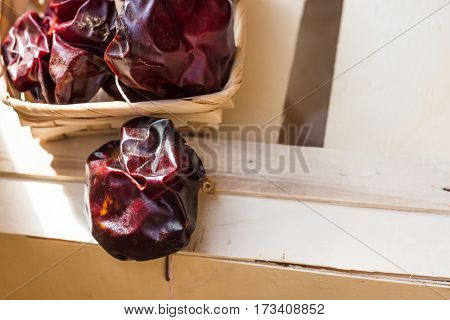 Spanish dried nyora pepper on thread in wicker basket on wood box bright red color sunlight spot top view close up