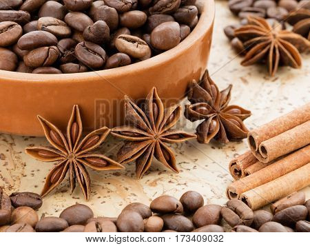 Black coffee beans lying on a clay dish. Cinnamon sticks and star anise star near the saucer of coffee beans on a cork board.