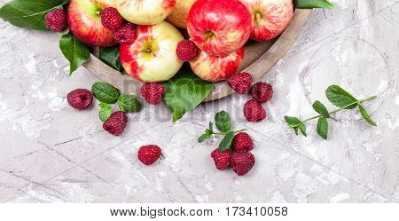 Fresh raspberries and apples on old wooden plate on a concrete background. Healthy concept. Natural healthy food. Organic food.