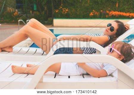 Endless summer Cute baby and mother relaxing at sunbed near pool at resort. A little girl wearing sunglasses. Child and mom sunbathe. Fashion girls, friends, family at resort