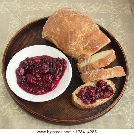Raspberry jam and bread. Jam has curative properties and delightful taste. It is cooked in house conditions.
