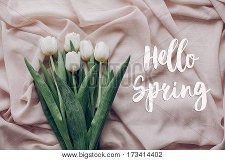 Hello Spring Text Fresh Sign. Instagram Spring Flat Lay. Stylish White Tulips On Beige Soft Fabric O