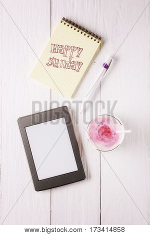 Berry smoothie and an inscription in notebook: Happy sunday. Flat lay