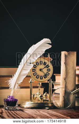 Literature concept. Inkstand with feather near magnifying glass old scroll and vintage clock against dark background with book