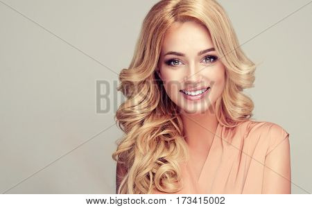 Beautiful girl blonde hair with an elegant hairstyle , hair wave ,curly hairstyle . Young woman with a beautiful smile and white teeth