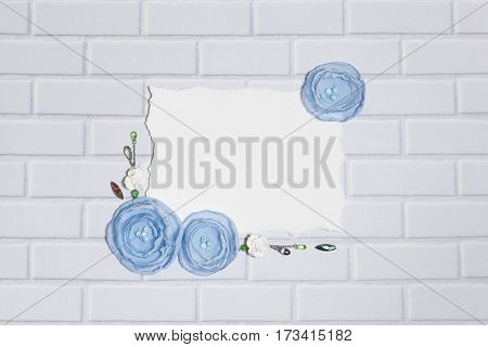White Background With Handmade Gentle Blue Ranunculus Flowers, Roses and Crystals, Lying Flat on the Light Gray Brick Wall, Top View. Have a Paper Empty Rectangular Place For Your Text.