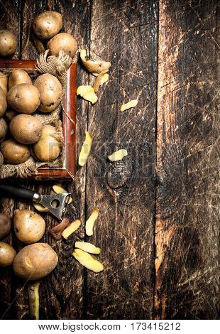 Fresh Potatoes In An Old Wooden Tray. On Wooden Background.