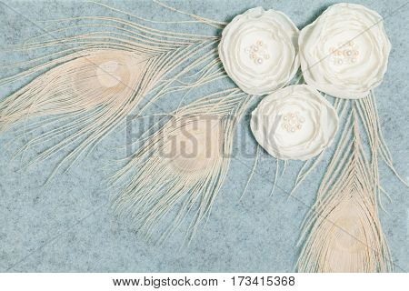 Light Gray Wool Rectangular Background With Handmade Gentle White Ranunculus Flowers and Peacock Feathers, Lying Flat, Top View. Have an Empty Place For Your Text.