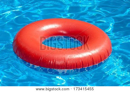 Inflatable red swim ring floating on a blue swimming pool