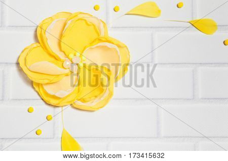 Close Up Background With Handmade Gentle Yellow Flower and Feathers, Lying Flat on the White Brick Wall, Top View. Have an Empty Place For Your Text.