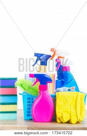 Spring cleaning concept - colorful spays and rubbers on wooden table border over white background