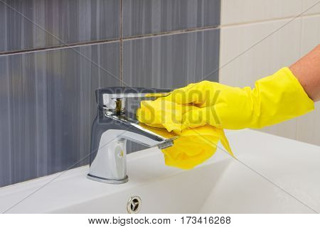 Spring cleaning, hands in yellow gloves washing tap bathroom