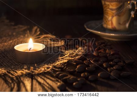 The candle burns near the bean and coffee Cup