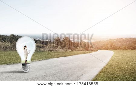 Young businesswoman trapped inside of light bulb on countryside road