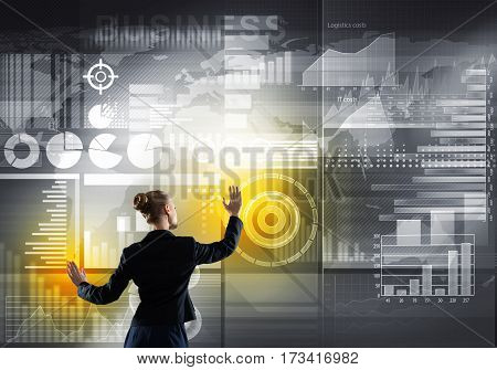 Rear view of businesswoman working with virtual interface