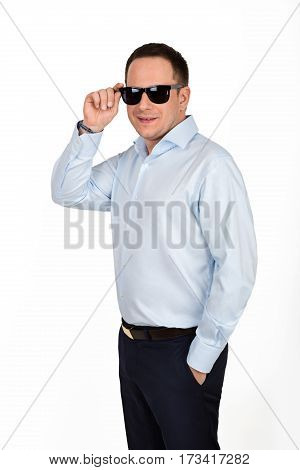 Portrait of a young handsome businessman in formal shirt and pants posing in black sunglasses on white background