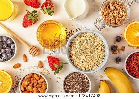 Ingredients for a healthy breakfast -  oatmeal, granola, honey, nuts, berries, fruits top view