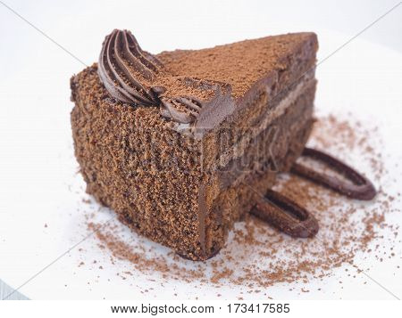 Food background. Piece of chocolate cake isolated on white. Slice of fresh brownie arranged on white plate.  Close-up image. Selective focus on the front.