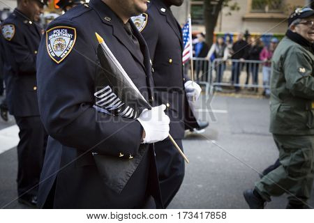 NEW YORK - 11 NOV 2016: A member of the NYPD carries a POW/MIA flag during the annual Americas Parade up 5th Avenue on Veterans Day in Manhattan.