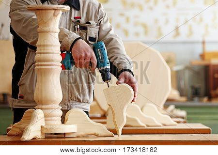 Professional woodworker with electric screwdriver in carpentry