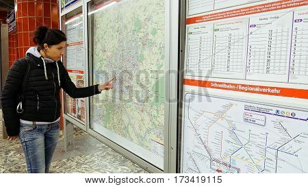 Hamburg, Germany - October, 10, 2016: Young woman looking at subway metro underground tube map on train station. Tourist use public transportation subway metro system in a big European city.