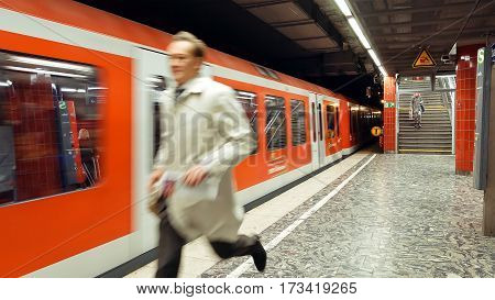 Hamburg, Germany - October, 10, 2016: Man is running to catch the arriving metro subway train. People use subway metro underground tube public transportation in a big European cities.