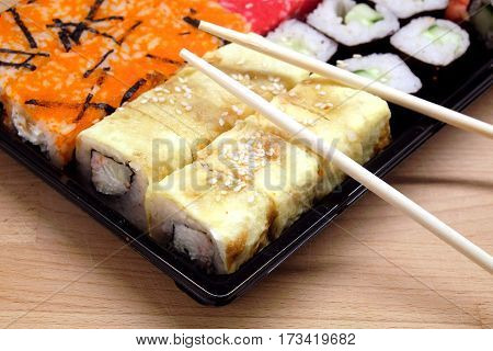 Sushi pieces on square tray on brown woode table side view closeup