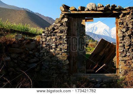 The village Kagbeni in the Himalayan mountains. Mountain View through a doorway. Nepal.