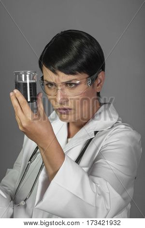 Medicine, Brunette woman in a laboratory, scientist studying a glass jar, wearing a white coat