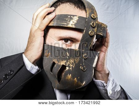 Frustrated, Angry businessman with iron mask on his face, is dressed in suit and tie